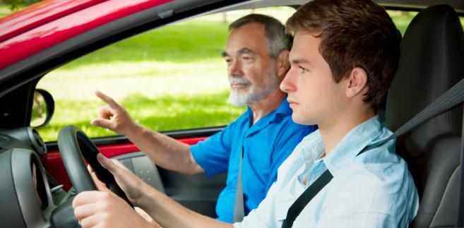 Młody kierowca podczas jazdy z instruktorem
