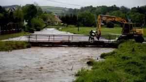 Strażacy obciążają betonowymi płytami most na wezbranej rzece Stupnica w Birczy, chcąc uchronić go przed zerwaniem przez wodę. Fot. PAP/Darek Delmanowicz