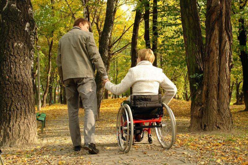 Kobieta na wózku inwalidzkim na spacerze w parku. fot. shutterstock.com